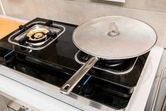 Silver metal frying pan covered with oil splatter screen. On gas stove Stock Photography