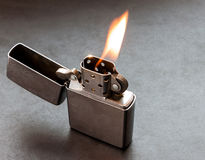 Silver metal lighter with flame. Royalty Free Stock Image