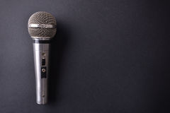 Silver metal microphone on black table top view. Silver metal microphone on black table. Top view. Horizontal composition royalty free stock photography