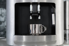 Silver metal mug is in the espresso machine Royalty Free Stock Images
