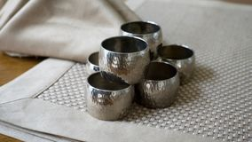 Silver metal napkin rings holders over a golden color place mat. Ready for table setting in an event, party or holiday. Silver metal napkin rings holders over a royalty free stock images