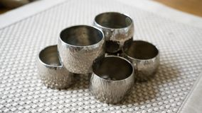 Silver metal napkin rings holders over a golden color place mat. Ready for table setting in an event, party or holiday. Silver metal napkin rings holders over a royalty free stock photo