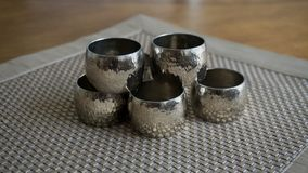 Silver metal napkin rings holders over a golden color place mat. Ready for table setting in an event, party or holiday. Silver metal napkin rings holders over a stock photography