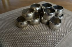 Silver metal napkin rings holders over a golden color place mat. Ready for table setting in an event, party or holiday. Silver metal napkin rings holders over a stock image