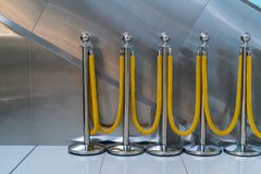Silver metal poles with yellow fabric rope barriers standing. By escalator background Royalty Free Stock Photo