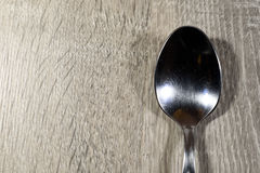 Silver Metal Spoon on Wood Kitchen Surface. Single shiny empty silver spoon on a wooden kitchen background Royalty Free Stock Photos
