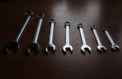 Silver  metal wrenches. The Set of silver metal wrenches on a wooden background Royalty Free Stock Photo