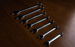 Silver  metal wrenches. The Set of silver metal wrenches on a wooden background Royalty Free Stock Images