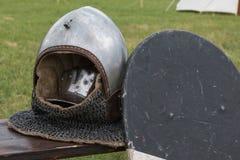 Silver and Metallic Knight Helmet near Black Shield Stock Photos