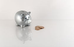 Silver Metallic Piggy Bank and Coins With Reflection Royalty Free Stock Photos
