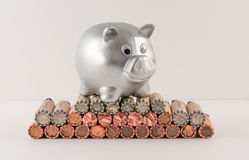 Silver Metallic Piggy Bank and Wrapped Coins Royalty Free Stock Photos
