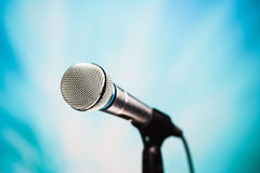 Silver microphone. Against blue background stock photos