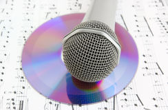 Silver microphone and cd on sheet of notes. Close up royalty free stock photography