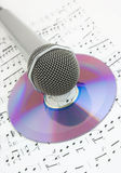 Silver microphone and cd on sheet of notes Stock Images