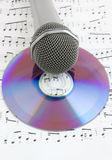 Silver microphone and cd on sheet of notes Royalty Free Stock Photography