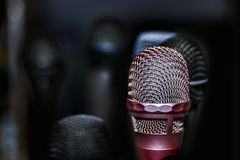 Silver microphone in a dark blurry background. Silver microphone in a dark blurry microphones background royalty free stock image