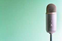 Silver Microphone Isolated on Mint Background. Silver microphone isolated on mint green background stock image