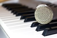 Silver microphone on the keyboard synthesizer. Music studio stock photography