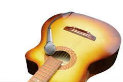 Silver microphone lays on acoustic guitar. On a white background royalty free stock photography