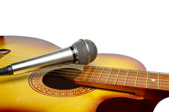 Silver microphone lays on acoustic guitar. On a white background stock photography