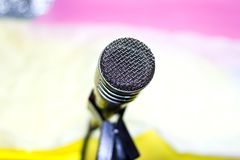 Silver microphone on rack closeup. Silver microphone on the rack closeup, colored background stock photography