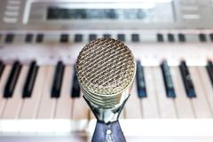 Silver microphone on rack closeup. Silver microphone on rack close-up. Keyboard synthesizer in the background royalty free stock photos
