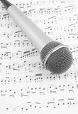 Silver microphone on sheet of notes. Close up stock photo