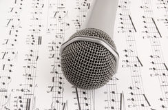 Silver microphone on sheet of notes Royalty Free Stock Images