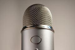Macro Silver Microphone on White Background. A silver microphone on white background stock photo