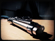 Silver 9mm pistol lying on a wooden table Royalty Free Stock Images