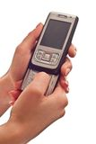 Silver mobile phone in hands Stock Images