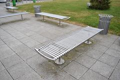 Silver modern benches on concrete. Benches in a park stock image