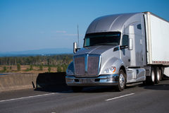 Silver modern big rig semi truck with trailer running on freeway. An amazing powerful professional silver big rig semi truck with a large comfortable cabin and a royalty free stock photography