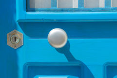 Silver modern doorknob on azure door closeup Royalty Free Stock Image
