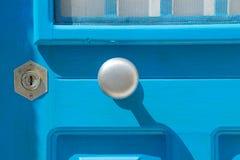 Silver modern doorknob on azure door closeup Royalty Free Stock Image