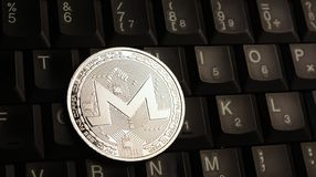 Silver Monero XMR coin on laptop keyboard. Silver Monero XMR coin over laptop keyboard royalty free stock images