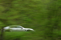 Silver motor car. Side view of silver motor car with green background and slow motion blur Stock Image