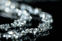 Silver necklace with diamonds close-up in defocus on a black background.  Royalty Free Stock Photography