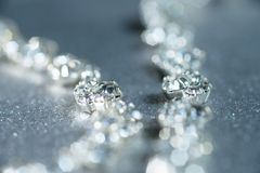 Silver necklace with diamonds close-up in defocus on a light background.  Stock Image