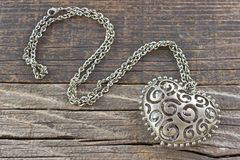 Silver necklace with heart pendant on wooden background Royalty Free Stock Image