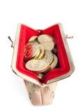 Silver- och guldmynt är i varm röd handväska arkivbild