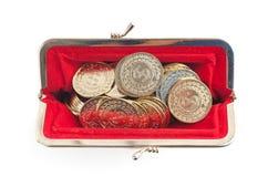 Silver- och guldmynt är i varm röd handväska arkivfoto