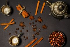 Silver old oriental teapot with coffee beans anise cinnamon on a black background. View from above. Silver old oriental teapot with coffee beans anise cinnamon Stock Photo