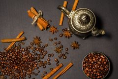 Silver old oriental teapot with coffee beans anise cinnamon on a black background. View from above. Silver old oriental teapot with coffee beans anise cinnamon Stock Images