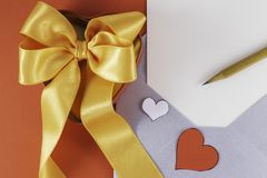 Silver open envelope with white blank letter and two red white hearts Wooden pencil Red box with big orange bow on it royalty free stock photography