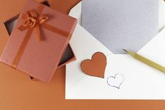 Silver open envelope with white blank letter and two small red and white hearts with giftbox stock photos