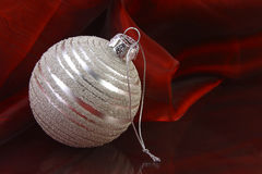 Silver Ornament. A silver ornament on red fabric Royalty Free Stock Image