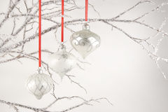 Silver Ornaments on Crystal Branches. Three silver Christmas ornaments hung with red ribbons from decorative crystal branches stock photo