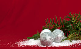 Silver ornaments with evergreen on red Stock Images