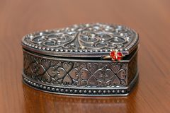 Silver ornate heart jewelry box on wood table with red ring. Silver ornate heart jewelry box on wood table royalty free stock photography